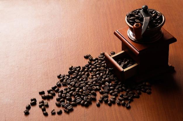 Кофейные зерна и деревянная кофемолка на деревянном столе