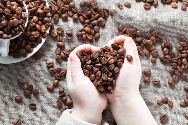 커피 원두는 아이의 손에, 커피 원두가 흩어져있는 식탁보와 머그잔에 있습니다.