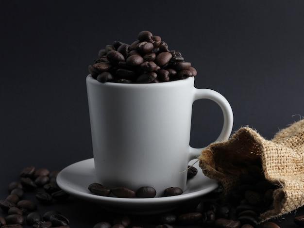 コーヒー豆は白いカップに入っており、床に散らばっています
