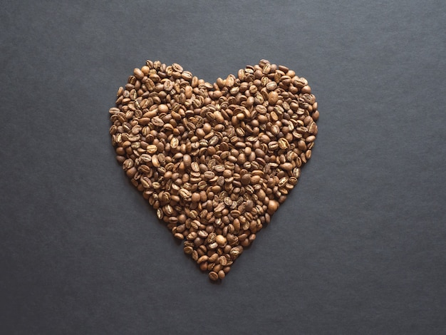 Coffee beans are laid out in the shape of a heart on a black table.