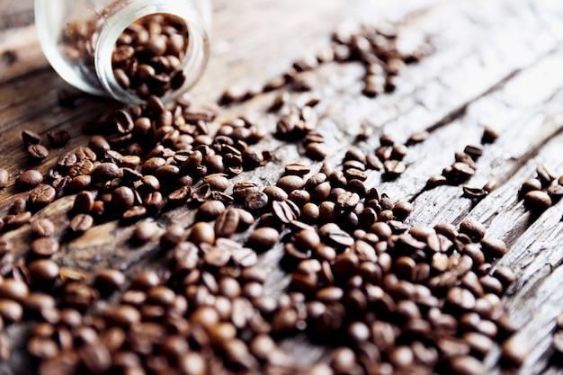 コーヒー豆はガラスの瓶と木製のテーブルの上にあります。