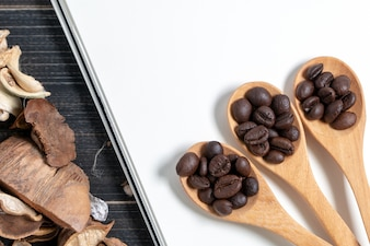 Coffee beans are placed in a wooden spoon on blank notebook and dried flowers