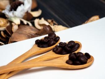 空白のノートブックとドライフラワーの木のスプーンにコーヒー豆を入れる