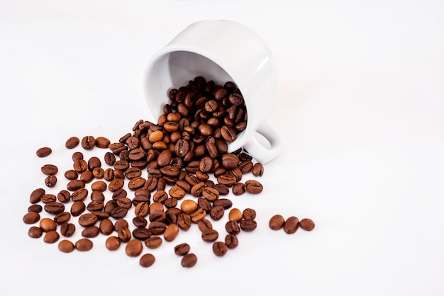 Coffee beans are scattered from a cup on a white background. copy space.