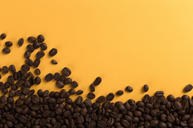 Coffee beans are scattered on a yellow paper  close-up, , commercial copyspace.