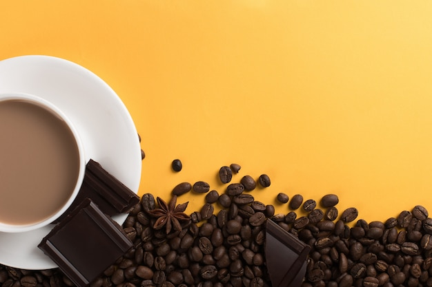 Coffee beans are scattered on a yellow paper  and a white cup, chocolate, , commercial copyspace.