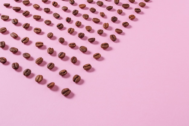 Coffee beans are spread out on a pink background