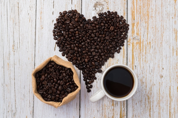 Coffee beans arranged in a heart shape, of coffee and a coffee mug on light wood background