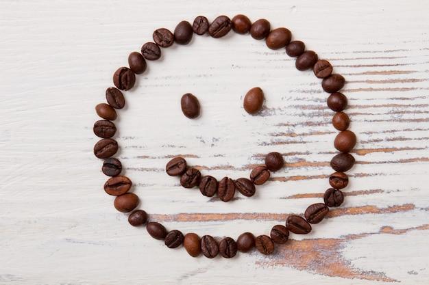 행복 한 웃는 얼굴에 배열하는 커피 콩. 흰색 목재 표면.