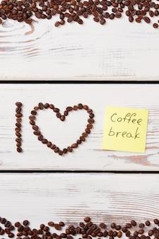 Кофейные зерна расположены в сердечке, и я письмо. желтый бумажный стикер с словом кофе-брейк. белая деревянная поверхность.