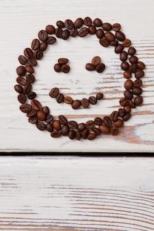 웃는 얼굴에 배열하는 커피 콩. 흰색 나무에 갈색 씨앗.