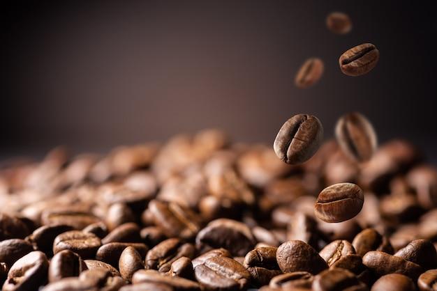 공장에서 커피 콩입니다. 커피 콩이 테이블에 떨어집니다. 복사 공간이 있는 신선한 커피 콩을 떨어뜨리는 배경