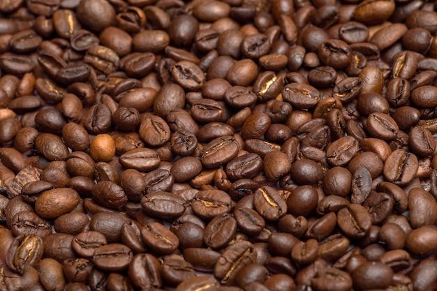 コーヒー豆の背景。コーヒー豆はテーブルの上にクローズアップ。コーヒーのコンセプト