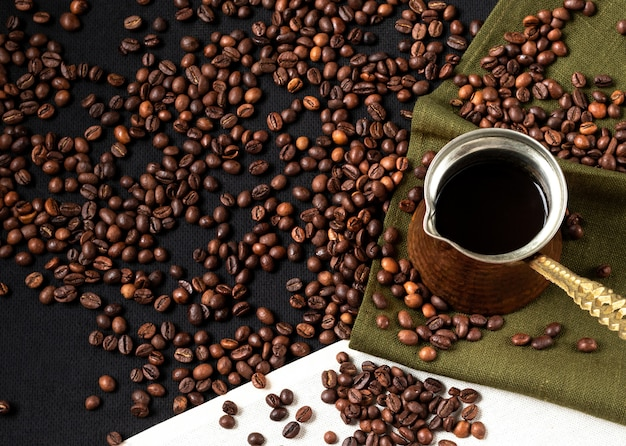 Coffee beans background. vintage cezve (turkish coffee) standing on coffee beans and linen napkin. layout design with copy space