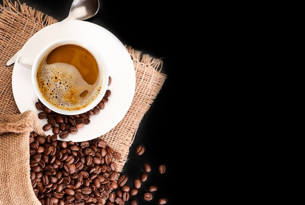 Coffee beans in a bag and a cup with aromatic coffee. top view