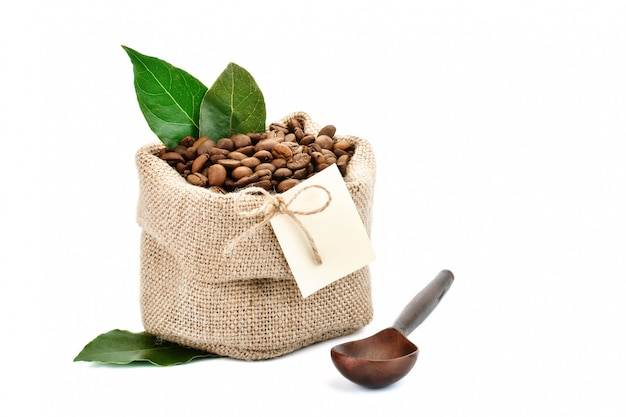 Coffee beans in a bag of sackcloth on white with blank tag.