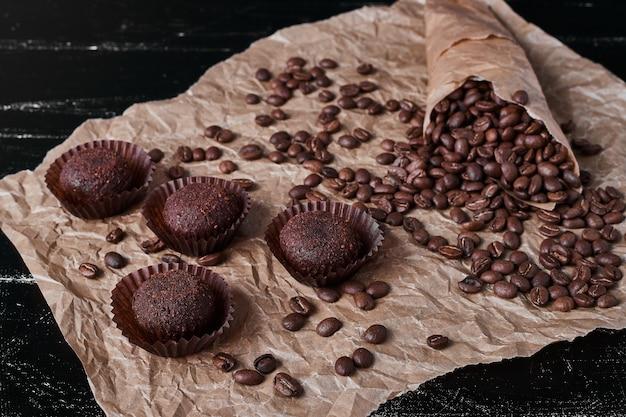 Chicchi di caffè su sfondo nero con praline di cioccolato.