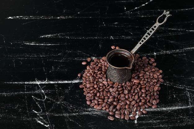 Chicchi di caffè su sfondo nero con una pentola metallica.
