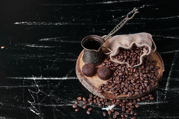 Coffee beans on black background with pralines.