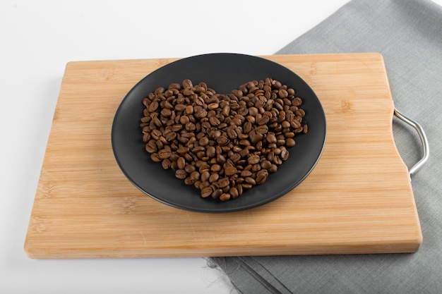 Coffee beans on black saucer