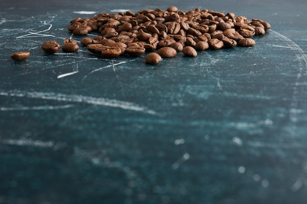 Coffee beans on blue table.