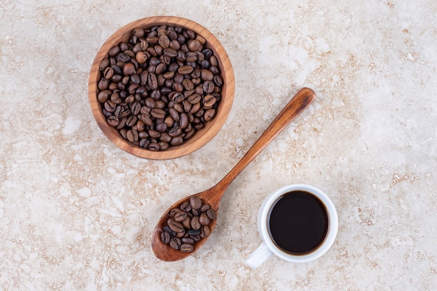 Coffee beans in a bowl and on a spoon next to a cup of coffee