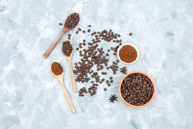 Chicchi di caffè in una ciotola e cucchiai di legno su uno sfondo grunge