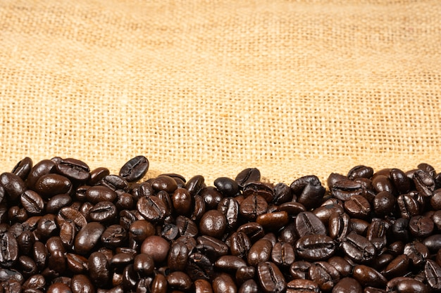 Coffee beans on brown linen fabric background. roasted coffee beans texture, used as a background. flat lay, top view, copy space.