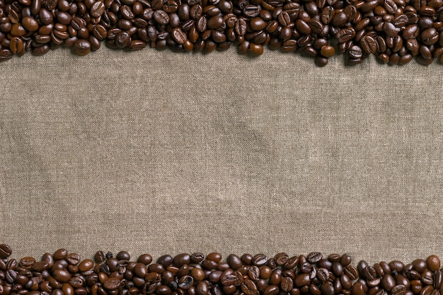 Coffee beans on burlap background. top view. copy space. still life. mock-up. flat lay