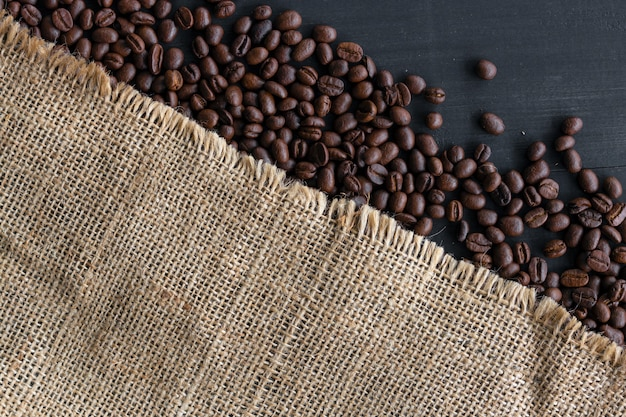 Coffee beans in burlap sack on old wooden background. top view