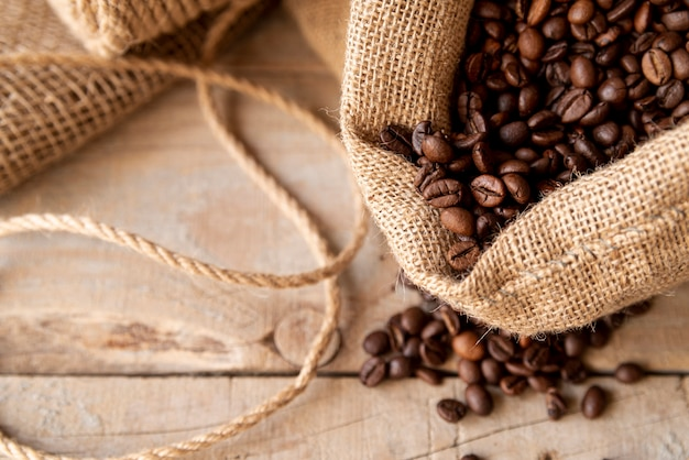 Coffee beans in burlap sack on plywood