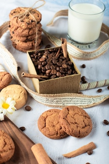 Coffee beans and butter cookies with a glass of milk on a blue tablecloth