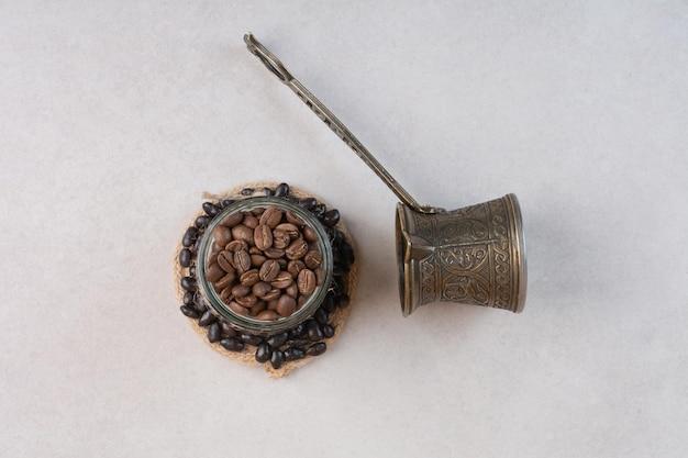 Chicchi di caffè e cezve su sfondo bianco. foto di alta qualità