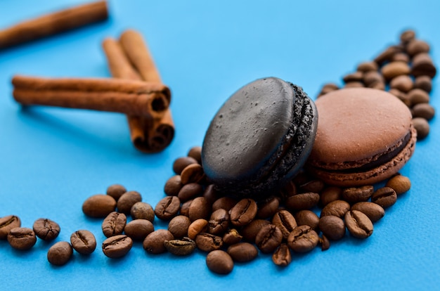 Coffee beans and chocolate macaroons on blue with a place under the text