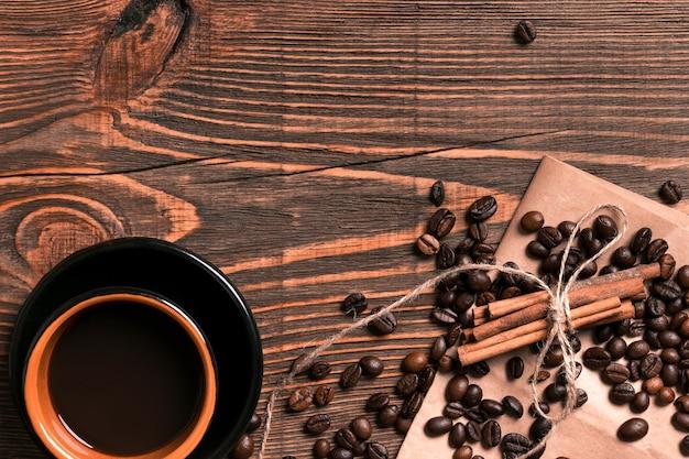 素朴な木製のテーブルにコーヒー豆、シナモンスティック、淹れたてのコーヒーを入れ、上から眺めてテキストを入れるスペースがあります。静物。モックアップ。フラットレイ