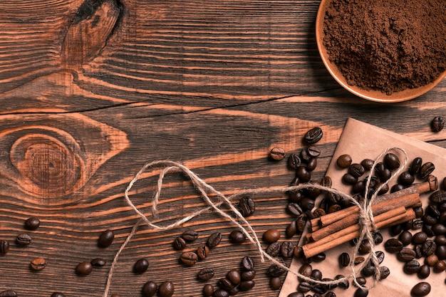 素朴な木製のテーブルにコーヒー豆、シナモンスティック、挽いたコーヒー、テキスト用のスペースを上から見たところ。静物。モックアップ。フラットレイ