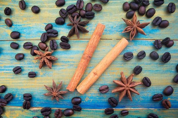 青と金で描かれた木製の背景にコーヒー豆、シナモンスティック、スターアニス。閉じる。