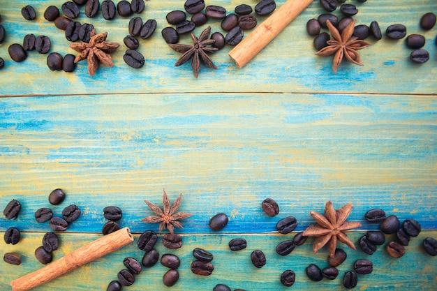 青と金で描かれた木製の背景にコーヒー豆、シナモンスティック、スターアニス。テキストの場所。