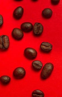 Крупный план кофейных зерен на красном фоне.