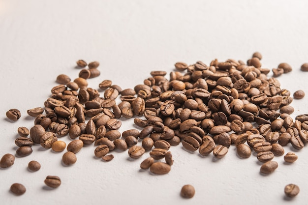 Coffee beans close up scattered on a light surface  space