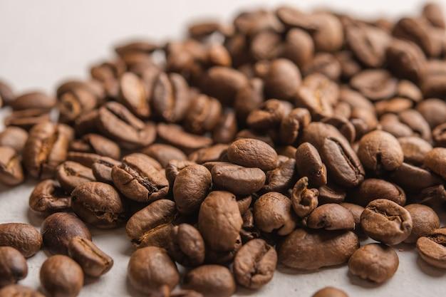 Кофейные зерна крупным планом, разбросанные на светлой поверхности, селективный фокус, крупным планом