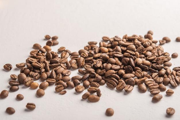Кофейные зерна крупным планом разбросаны на светлой поверхности