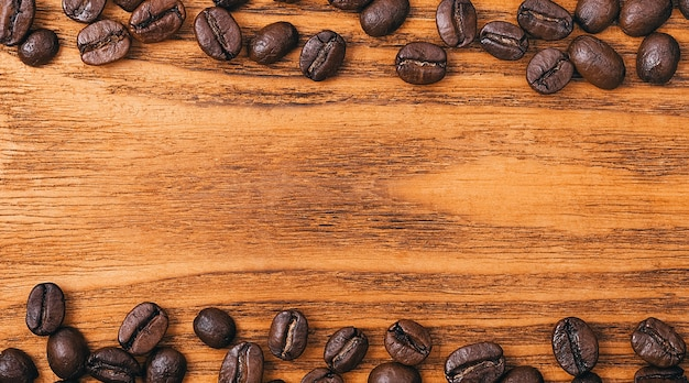 Coffee beans close-up scattered on a table made of textured wooden boards..