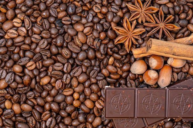 Coffee beans close up, top view cinnamon, hazelnuts and chocolate, background image