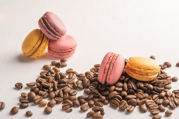 Coffee beans closeup scattered on a light surface multicolor macarons lie on top  space
