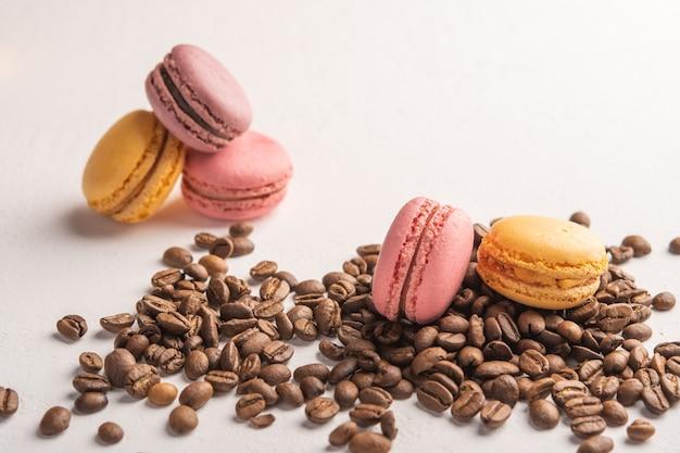 Крупный план кофейных зерен, разбросанных по светлой поверхности, разноцветные макароны лежат на верхнем пространстве
