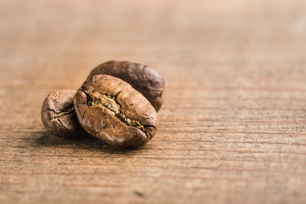 Coffee beans closeup on wooden background with copyspace
