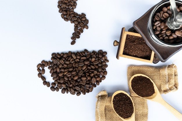 Coffee beans in coffee cup shaped with wooden grinder and sack