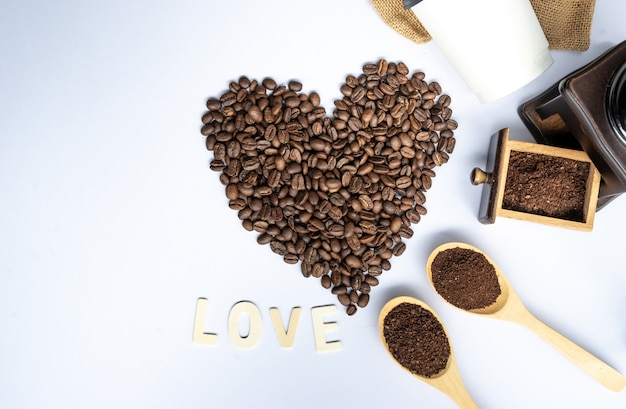 Coffee beans in coffee heart shaped with wooden grinder and sack