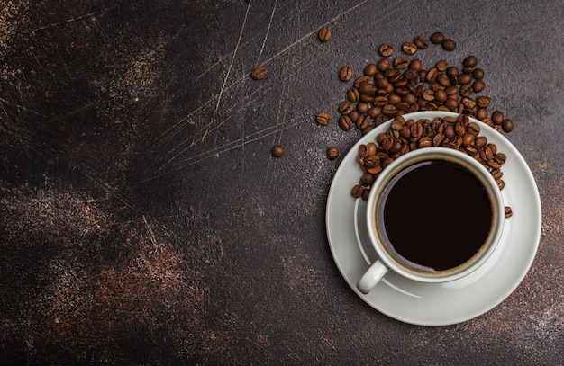 Coffee beans and coffee in a white cup on a dark rusty background. top view, copy space